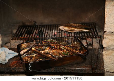 Fish grill / There are fish on the grill and grilled. An raw freshwater fish on the grill. Cooked in traditional style. Cooking of salted fish on a grill stove.