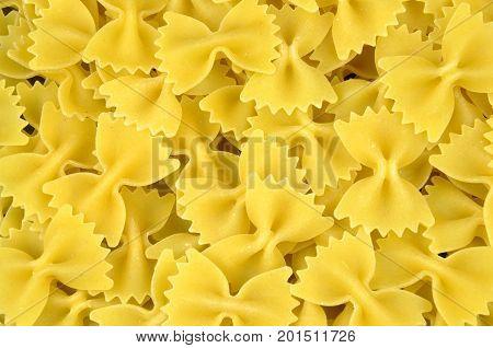 Farfalle background. Raw yellow pasta, tied bows