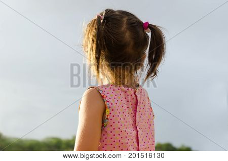 Little Girl With Pigtails In Pink Dress Looking At The Sunset