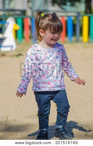 Little Girl Standing And Smiling In The Park Wearing Denim Trousers And Flowers T Shirt