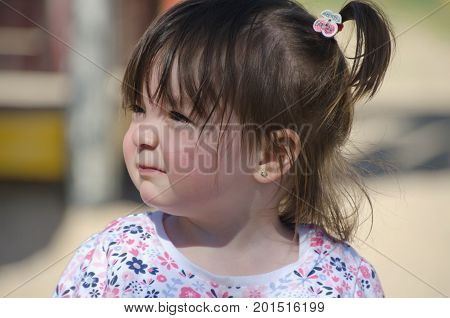 Little Girl With Pigtails And A Shirt With Little Flowers In Blue And Pink
