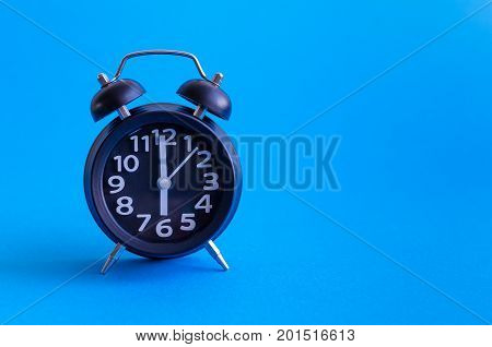 Alarm clock with six o'clock on yellow background in retro pop art style with place for text. Wake up concept. Back to school. Copy space.