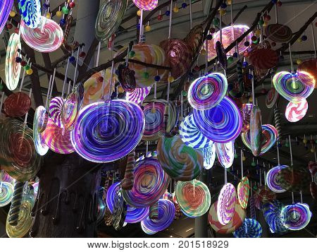 Numerous colorful lollipop candies hanging illumintated light