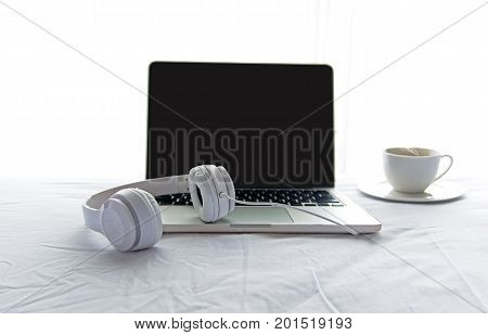 Morning music background. Coffee with laptop in white bed sheet duvet and pillow messed up. Music and Lifestyle Concept.