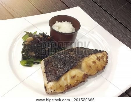Smoked fish by charcoal stove with green fresh seaweed and chopped smash radish are delicious and healthy Japanese food.