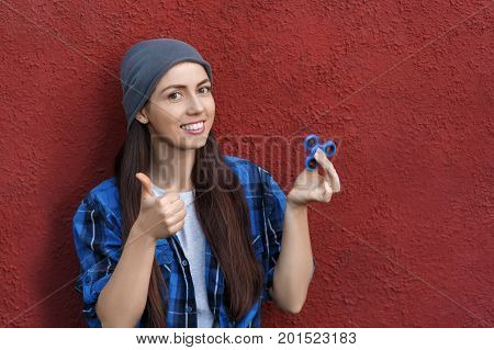 hipster girl playing with fidget spinner. Portrait of young woman with rotating spinner. Popular trendy stress relieving toy