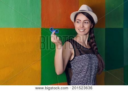 happy girl playing with fidget spinner. Portrait of young woman holding rotating spinner. Popular trendy stress relieving toy