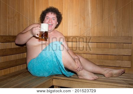 Funny fat man in a sauna with a beer.