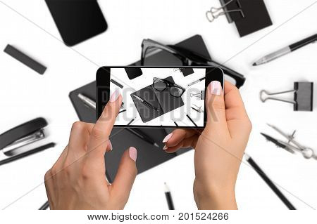 Shooting black stationery on phone's camera. Stationery on white background. Close-up woman's hand holding phone.