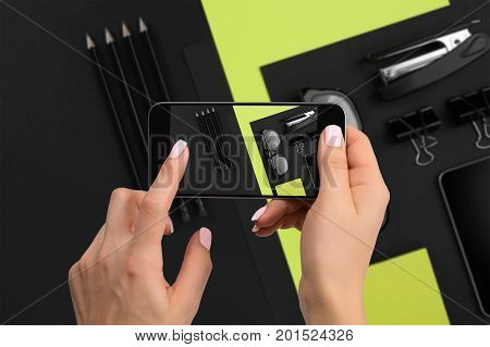 Shooting black stationery on phone's camera. Stationery on black-green background. Close-up woman's hand holding phone.
