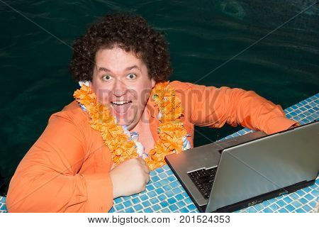 Funny man with laptop in the pool. Vacation and work.