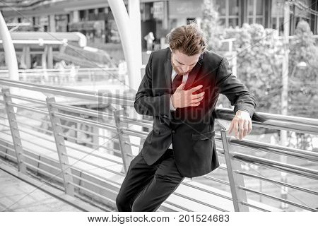 Businessmen is having a heart attack and holding hand on the chest