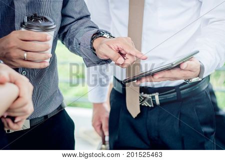 Group Of Business People Talking Withbusinessman Working On Digital Tablet In Outdoor After Work