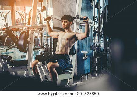Fitness man exercising at the gym on a machine strong bodybuilder doing heavy weight exercise
