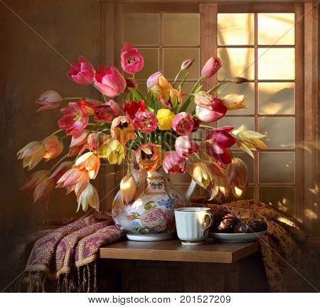 household still-life-vase of flowers, a glass of tea, chocolate, sweets, chromatic background, dishes, plants, window, table.