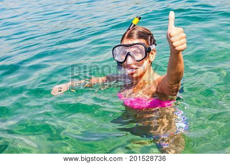 Young woman doing snorkeling in Trogir Croatia in the clear turquoise water showing thumbs up