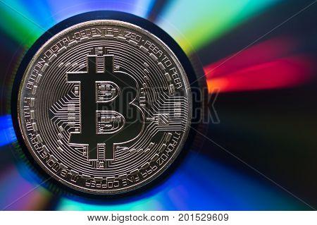 Golden bitcoin on a reflective iridescent surface