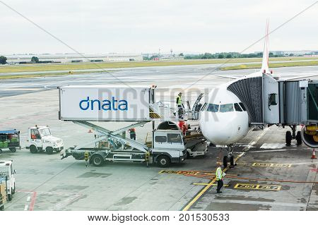 PRAGUE, CZECH REPUBLIC - JUNE 16, 2017: Vaclav Havel Prague International Airport, Ruzyne, Czech Republic. Personnel loading luggage into a plane in an airport.