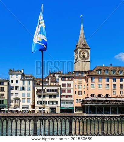 Zurich, Switzerland - 18 June, 2017: city's old town buildings along the Limmat river, clock tower of the St. Peter Church. Zurich is the largest city in Switzerland and the capital of the Swiss canton of Zurich.