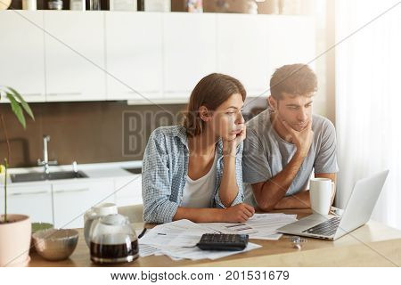 Portrait Of Family Couple Looking Attentively Into Screen Of Laptop, Sitting At Kitchen Table, Surro