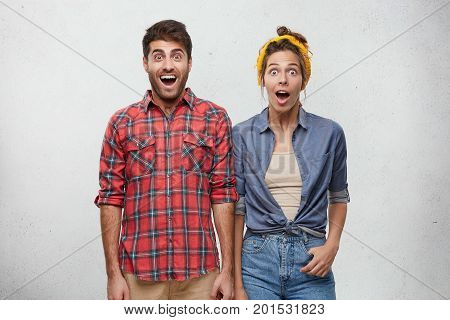 Surprise And Astonishment Concept. Picture Of Funny Emotional Young European Couple Wearing Fashiona