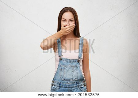 European Woman In Denim Overalls, Covering Mouth With Hand Trying To Keep Silence And Not Telling Se