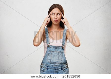 Cute Young Woman In Denim Jumpsuit Holding Fingers At Her Temples And Looking Sideways With Concentr