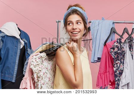 Positive Female Standing Sideways Holding With Hangers Of Clothes On Shoulders, Looking Aside Waitin