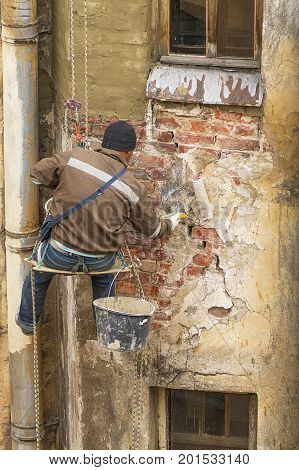 The worker in the stall equipment at the height repairs the wall of the building, beats off the old plaster and covers the mortar with mortar
