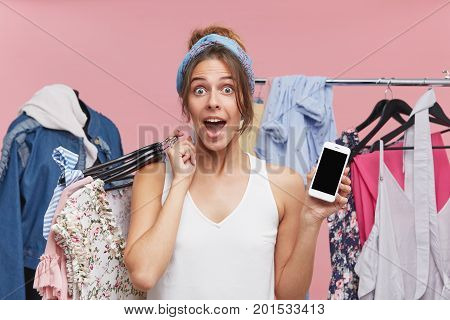 Excited Woman Looking With Great Surprisment Into Camera, Holding Hangers With Clothes While Standin