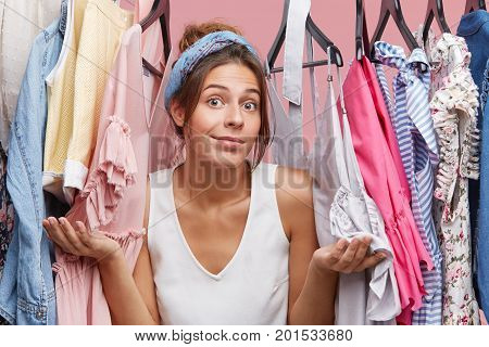 Female Model In Casual Clothes, Shrugging Her Shoulders While Standing Near Her Wardrobe, Having Hes
