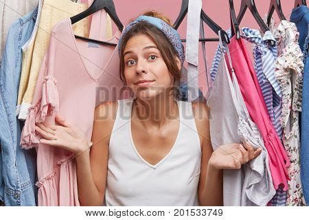 Cute European Woman Wearing White T-shirt, Feeling Uncertainty While Looking Through Rank With Cloth