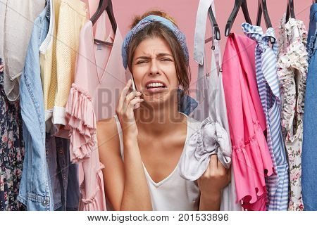 Upset Woman Standing Near Rack Of Clothes, Chatting Over Smart Phone With Her Friend, Complaining Th
