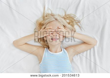 Adorable Little Girl Lying On White Bedclothes, Covering Her Eyes With Hands, Wearing Sailor T-shirt