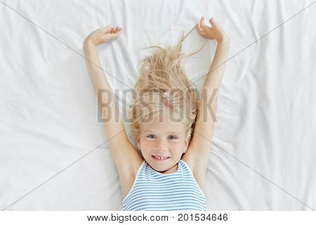 Lovely Little Child With Blue Eyes And Freckles Stretching In Bed In Morning, Looking Joyfully Into