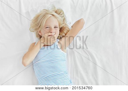 Small Child With Blonde Hair, Blue Eyes And Freckled Skin, Lying In Bed, Covering Mouth With Hand An