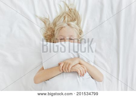 Carefree Restful Little Girl Lying On White Bedclothes, Embracing Pillow While Having Pleasant Dream