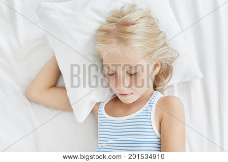 Pleasant Looking Little Girl With Blonde Hair And Freckled Face, Having Sweet Sleep While Lying On W
