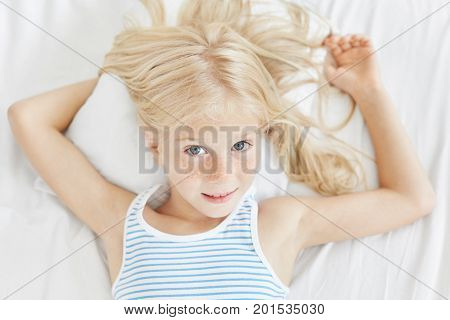 Lovely Blue Eyed Freckled Girl With Light Hair, Wearing Striped T-shirt, Lying On White Pillow In Be
