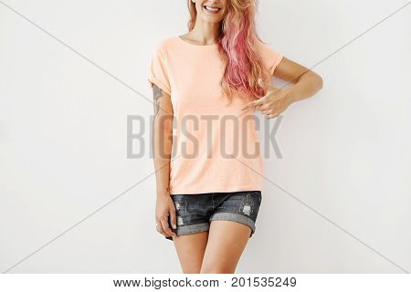 Cropped Shot Of Stylish Smiling Woman Wearing Loose T-shirt And Jean Shorts, Pointing At Copy Space