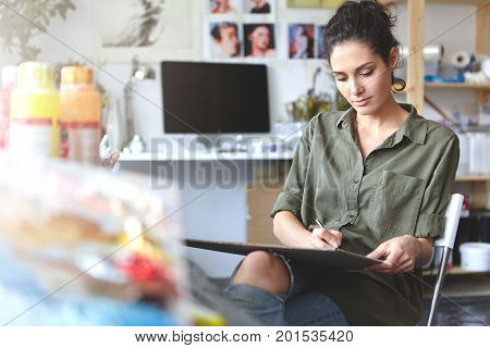 Female Artist Dressed Casually, Working On Her Sketch While Drawing Something And Sitting In Her Wor