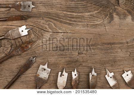 Old metal spade bits for drilling wood lie wooden background. View from above