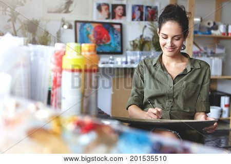 Good-looking Cheerful Professional Young Female Artist Working On New Creative Project, Drawing, Mak