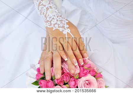 Bride and groom holding hands outdoors and flowers