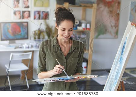 Portrait Of Cute Female Artist Working In Workshop, Painting With Brush And Watercolors, Standing Ne