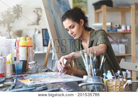 Picture Of Serious Concentrated Young Caucasian Female Artist Sitting At Desk With Painting Accessor