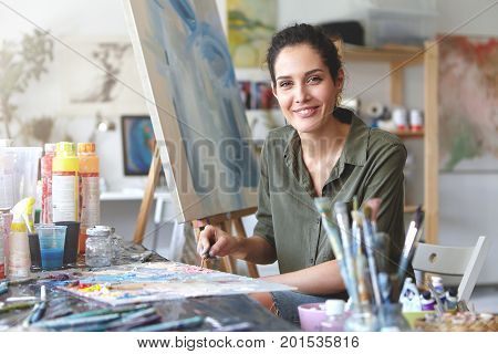 Portrait Of Gorgeous Excited Young Brunette Female Artist In Casual Blouse Of Khaki Color, Mixing Oi