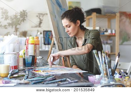 Serious Brunette Young Beautiful Woman Sitting In Art Studio, Taking Colorful Paints From Tube While
