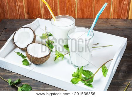 Coconut vegan milk coctail in glass on wooden background.