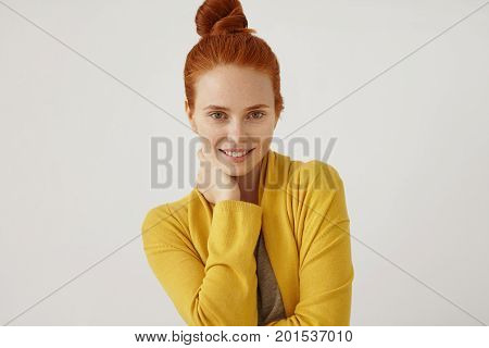 Portrait Of Beautiful Girl With Red Hair Bun, Freckled Skin, Keeping Hand On Neck, Wearing Yellow Sw